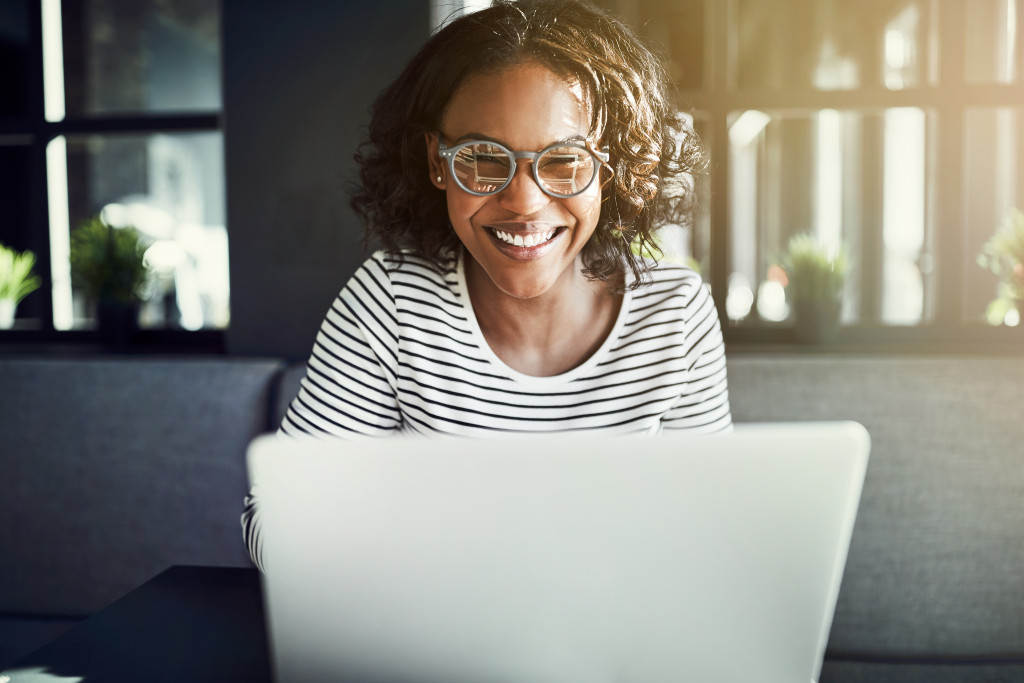 female using her laptop while smiling
