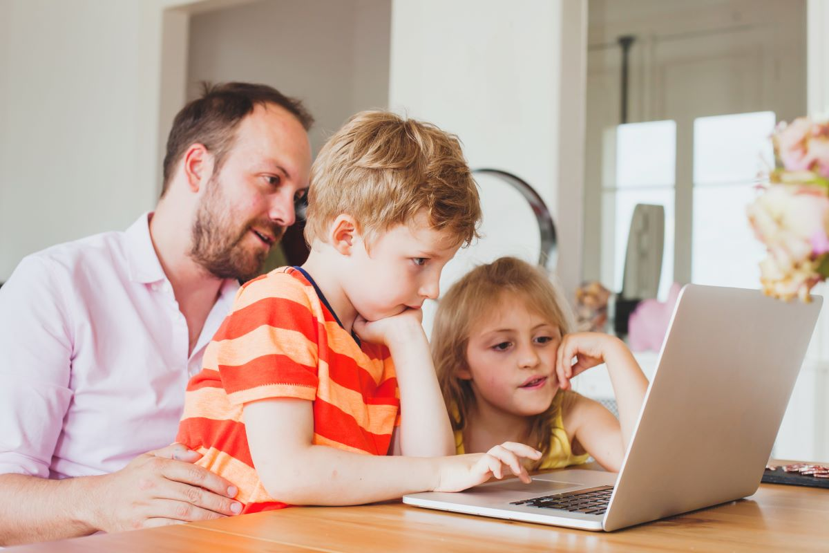 man letting kids use his laptop