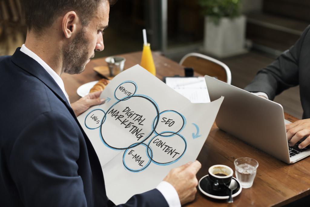 man holding digital marketing graphics